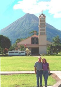 Ron and Linda Laytner before a modern church  in the town of Fortuna, which lies directly in the path of the giant Arenal Volcano which erupts from time to time. Photo from Edit International.